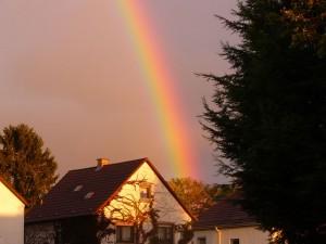 Rainbow Over A House At Sunset