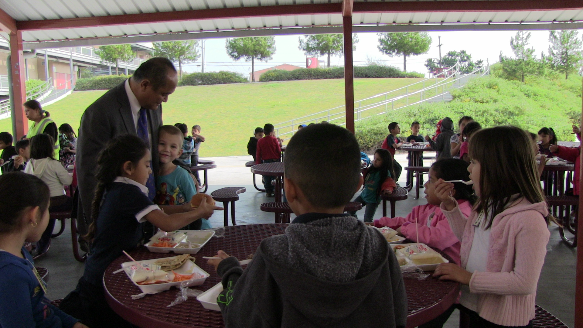 It takes Principal Godwin Higa a while to walk through the lunch courtyard. Every few steps, a child runs up to talk with him.