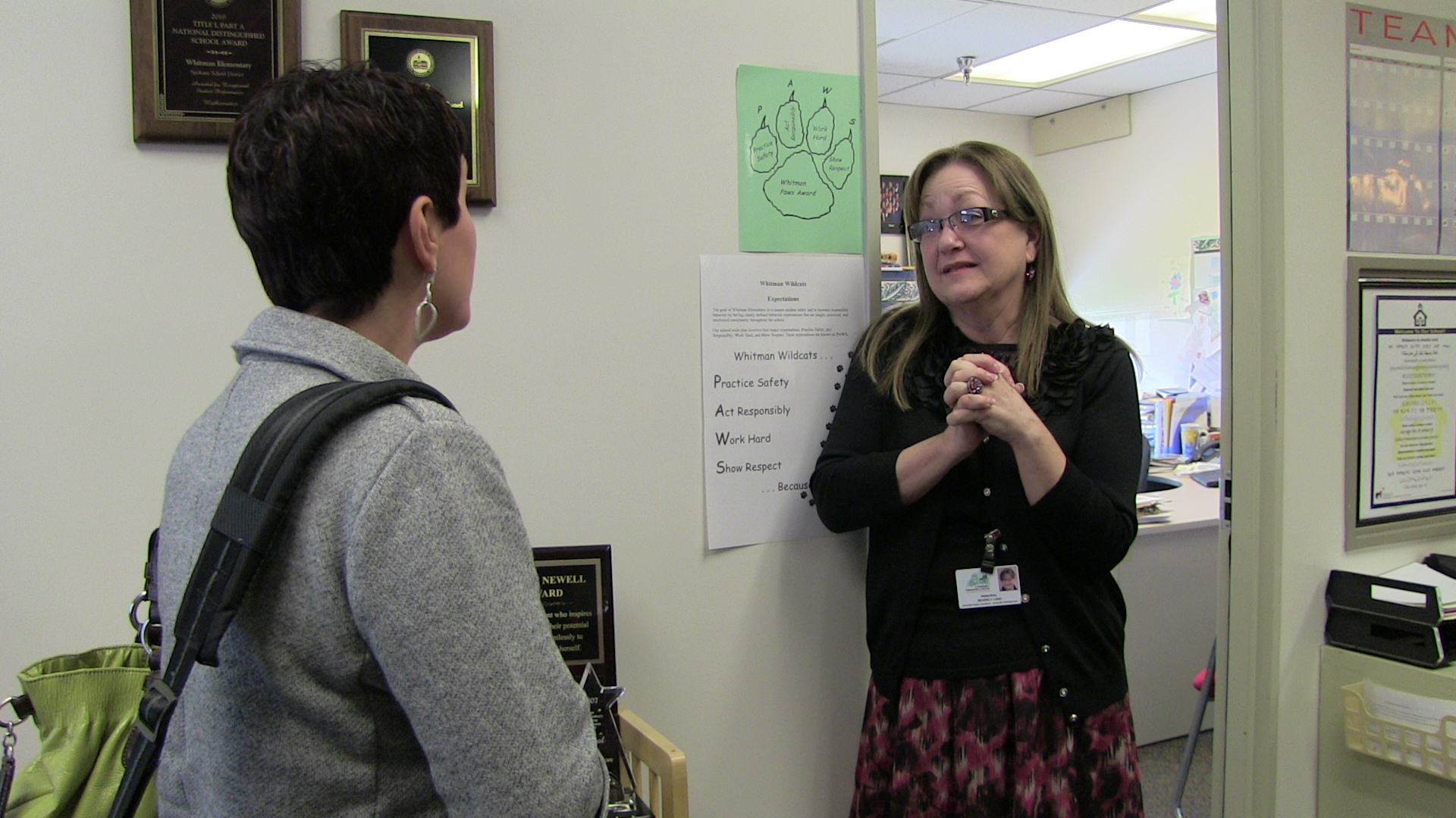 Beverly Lund, principal of Whitman Elementary School talks with Natalie Turner (back to camera).